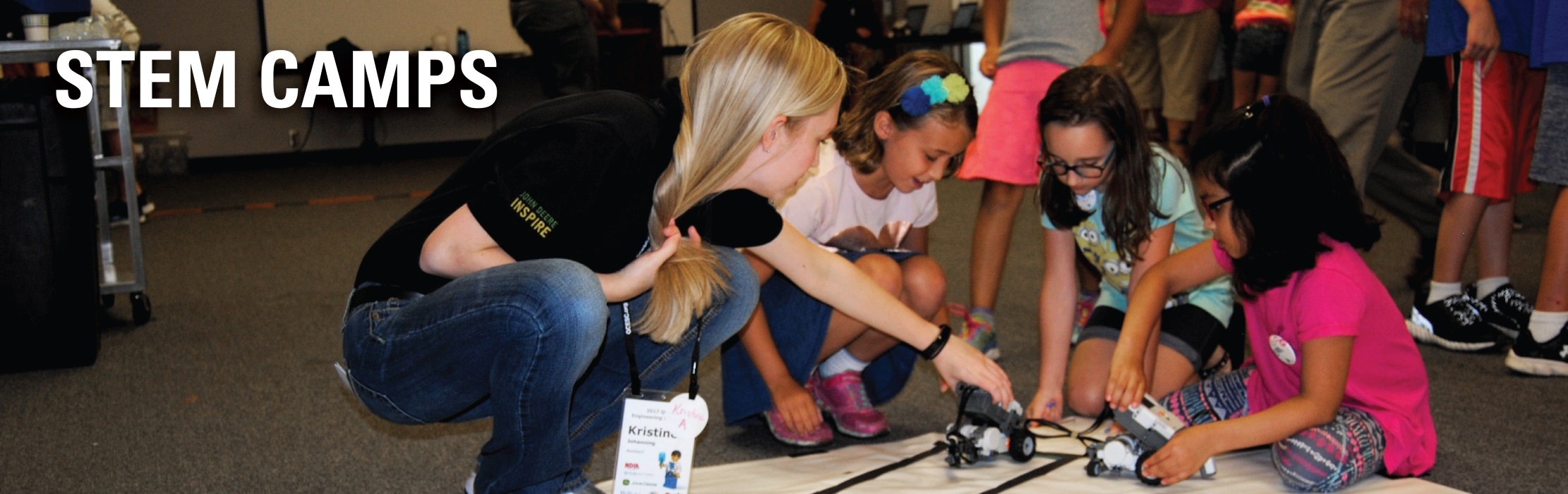 Industry engineer mentoring young girls at an ISU STEM camp.