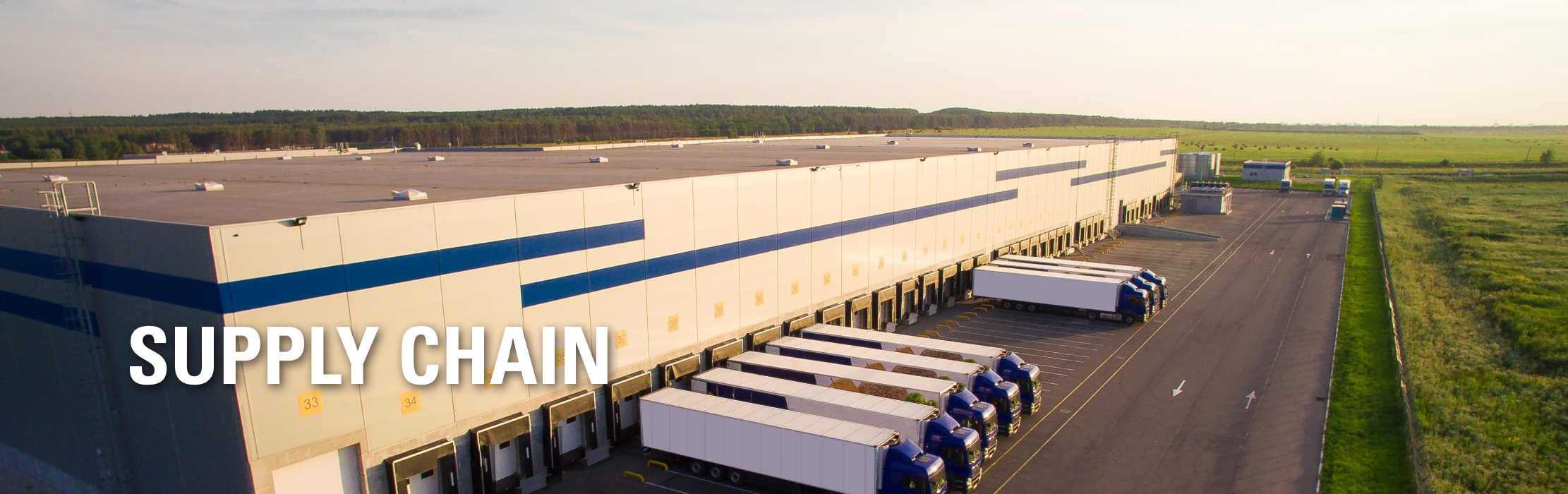 Trucks loading and unloading at a warehouse: Supply Chain.