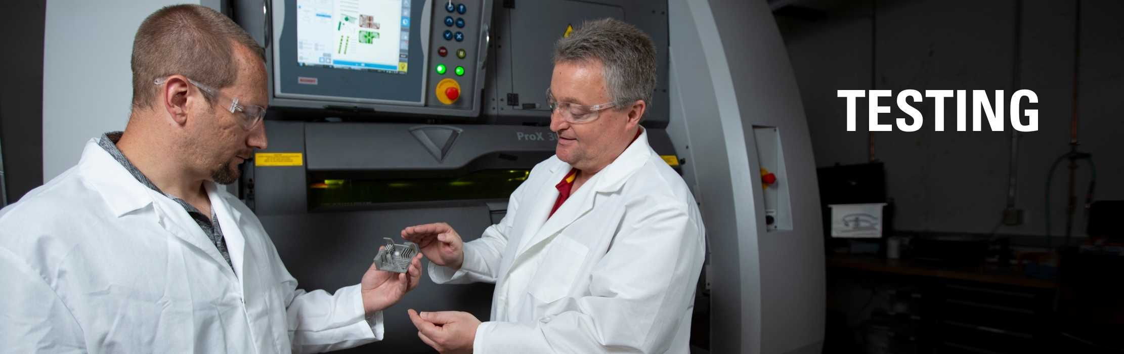 Two engineers examining a product manufactured with a metal additive manufacturing machine: Testing.